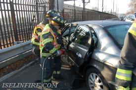 "FF Mary Bausch begins to extricate the driver using the ""Jaws of Life""."