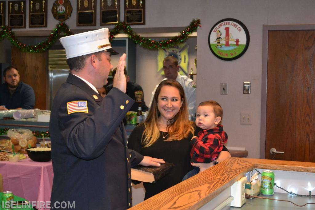 Chief Robert McPartland being sworn in. Holding the bible is his wife Nicole and son Caden.